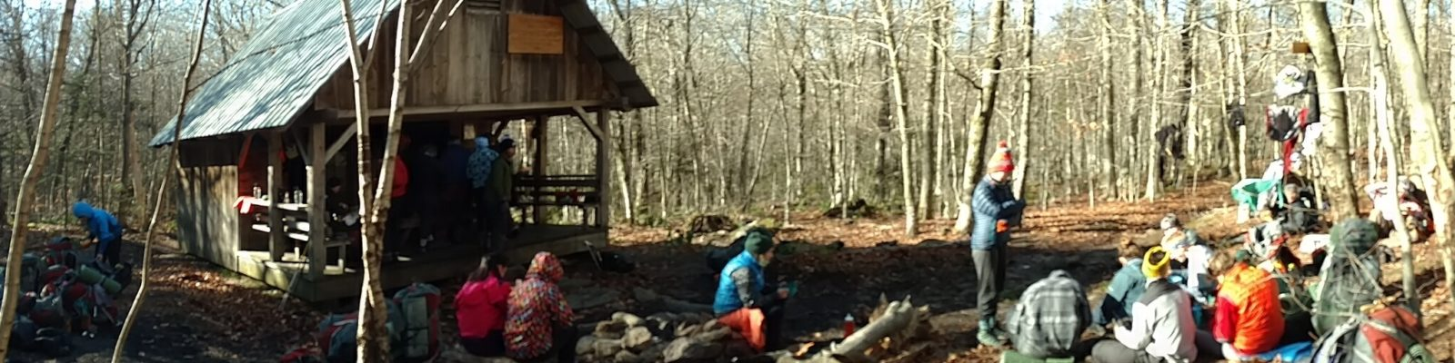 Group of hikers sitting outside the Stratton Mountain shelter in late fall